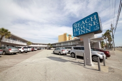 Exterior of Beach House Inn with parking lot and signage