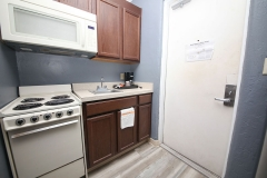 Room efficiency kitchen with oven, stove, microwave, sink, and coffee maker