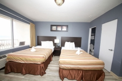 Two guest beds with striped comforters at Beach House Inn